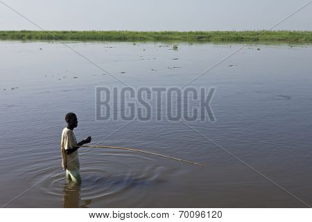 BOR, SOUTH SUDAN-DECEMBER 3 2010: An unidentified man fishes in the White Nile river of South Sudan.
