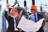 picture of substation  - happy managers discussing blueprint at electrical substation - JPG