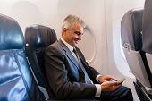 picture of cell  - happy middle aged businessman using cell phone on airplane - JPG