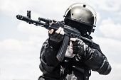 stock photo of rifle  - Spec ops soldier in black uniform and face mask with his rifle - JPG