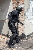 picture of anti-terrorism  - Spec ops soldier in black uniform and face mask aiming his pistol