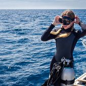 stock photo of goggles  - Beautiful, Caucasian woman diver on a boat in the ocean putting on goggles in preparation for scuba diving.