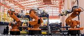 foto of robotics  - Modern Industrial Robotic Arms at assembling process - JPG