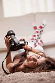 pic of lolita  - girl with a dslr camera on the floor of a living room smiling at camera in front of a sofa - JPG