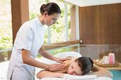 stock photo of day care center  - Side view of an attractive young woman receiving back massage at spa center - JPG