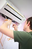 stock photo of insert  - Young worker inserts an orange water pump in air conditioning - JPG