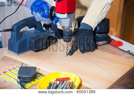 Craftsman use an electric drill, selective focus