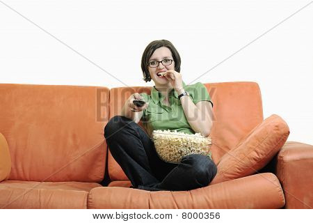 Young Woman Eat Popcorn On Orange Sofa