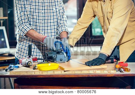 Home improvement - handyman sanding wooden floor in workshop