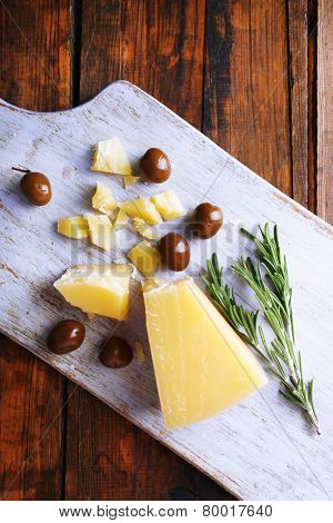 Parmesan cheese on cutting board with sprig of rosemary and olives on wooden table background