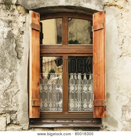 Window with wooden shutters and lace curtains.