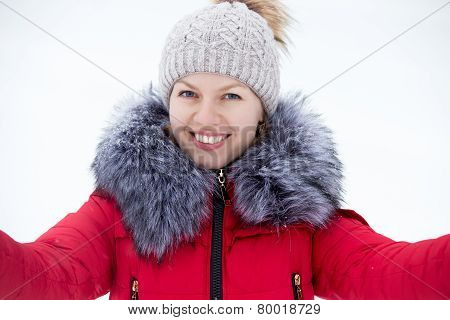 Happy Young Female In Red Winter Jacket Taking Self-portrait, Outdoors Against The Snow