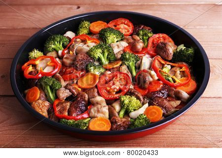 Braised wild mushrooms with vegetables and spices in pan on table