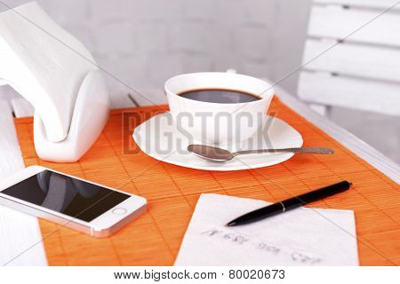 Cup of coffee with pen and phone number on napkin on table with orange bamboo mat, on white wall background