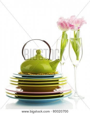 Stack of colorful ceramic dishes and flowers, isolated on white