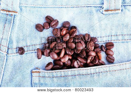 Coffee beans on the light blue jeans background