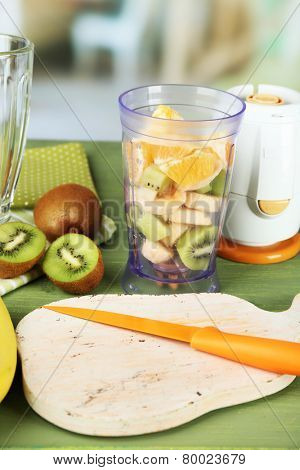 Sliced fruits and blender on wooden table, on bright background
