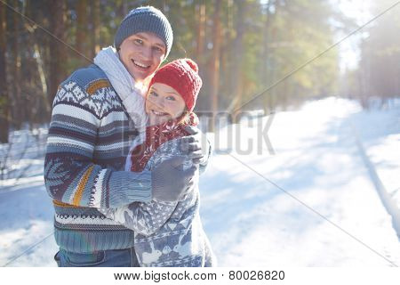Amorous couple in casual winterwear looking at camera outdoors