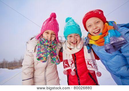 Group of joyful children in winterwear looking at camera