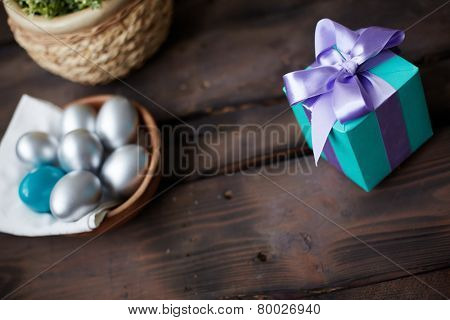 Blue giftbox with violet ribbon and painted Easter eggs near by