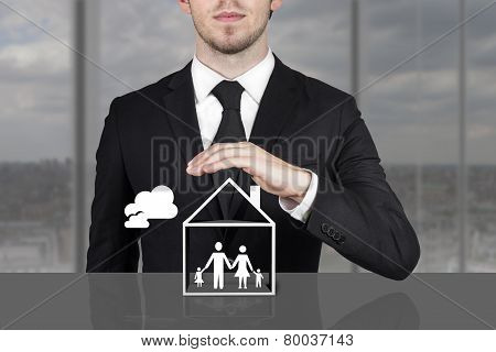 Businessman Holding Protective Hand Above Family Home