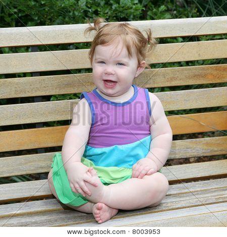 Niña de una año de edad en un banco del Parque