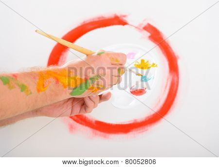 Hand holding paintbrush with artist palette, canvas on easel in a background
