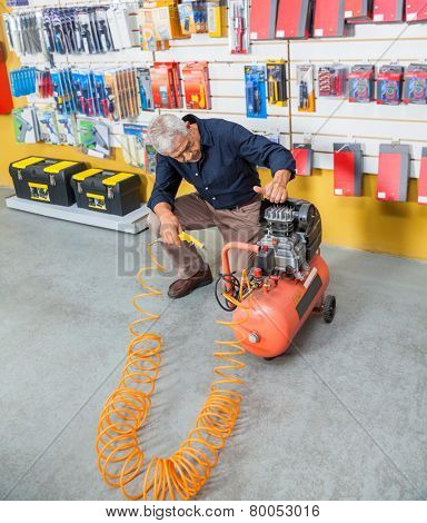 Full length of senior man examining air compressor in hardware shop