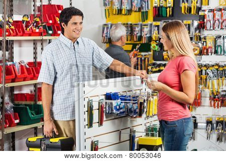 Smiling couple looking at each other while choosing tools in hardware store