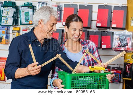 Happy male worker showing folding ruler to customer in hardware shop