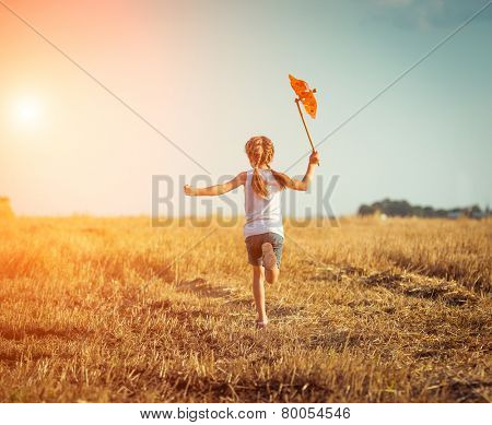 cute little girl in summer day holds windmill in hand