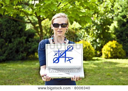 Young blonde woman with computer in the garden.