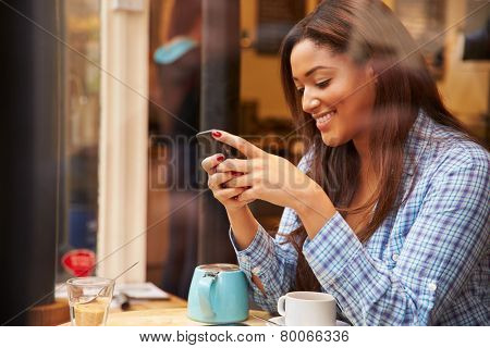 Woman Viewed Through Window Of Caf�?�¢?? Using Mobile Phone