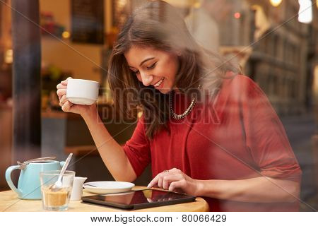 Woman Viewed Through Window Of Caf�¢?? Using Digital Tablet