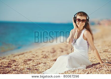 Beautiful brunette enjoying your favorite music on the beach