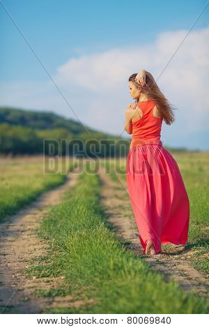 Portrait of young beautiful woman in long red dress standing back on the road in the field outdoor