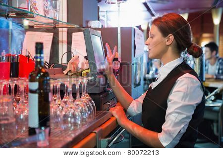 Happy barmaid using touchscreen till in a bar
