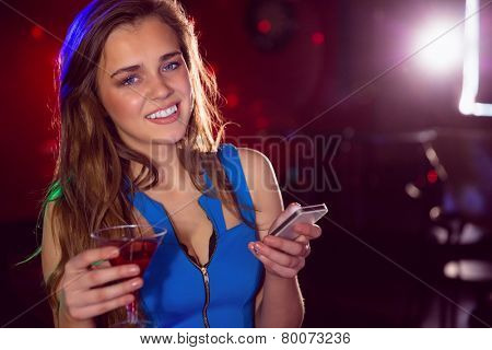 Pretty girl drinking a cocktail and texting at the nightclub