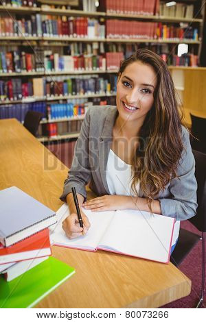 Smiling brunette student doing her assignment in library