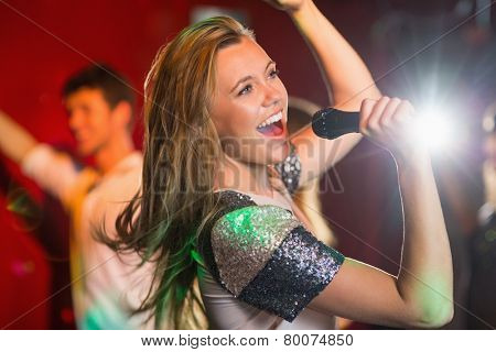Happy blonde singing karaoke into mic in a bar