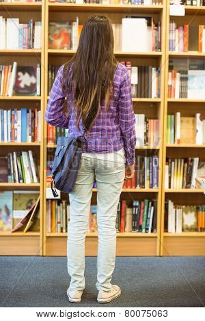 University student standing in the bookcase at the university