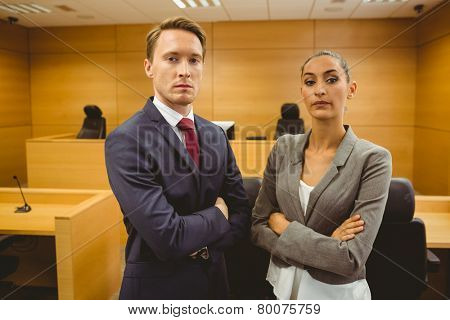 Unsmiling lawyers looking at camera crossed arms in the court room