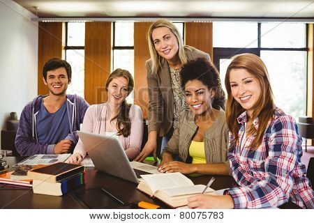 Student smiling at the camera with their teacher in library
