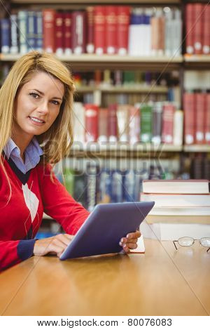 Smiling mature student using her laptop in library