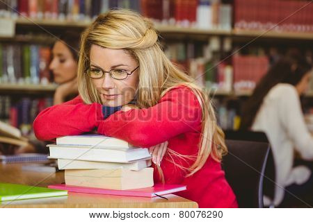 Thoughtful mature student leaning on a stack of books in library