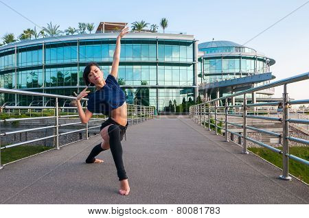 Girl stands in acrobatic positions, lifting his hands up. Acrobatics, ballet, dance. Outdoor