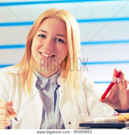 Young student woman medical / scientific researcher / doctor looking at a test tube of liquid in science laboratory, blood test