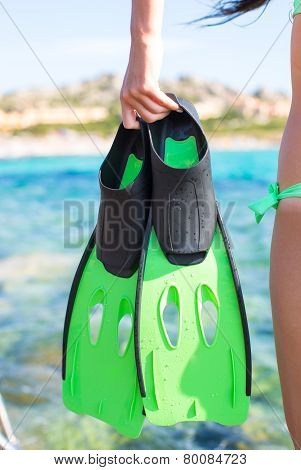 Diving goggles, snorkel and snorkeling fins at woman hands