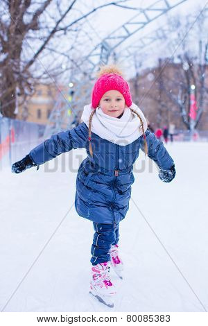 Adorable little girl skating on the ice-rink