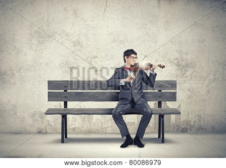 Young man in suit sitting on bench and playing violin